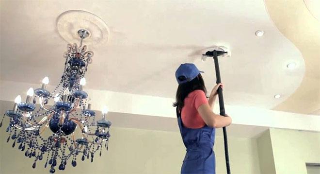 Девушка моет тканевый потолок