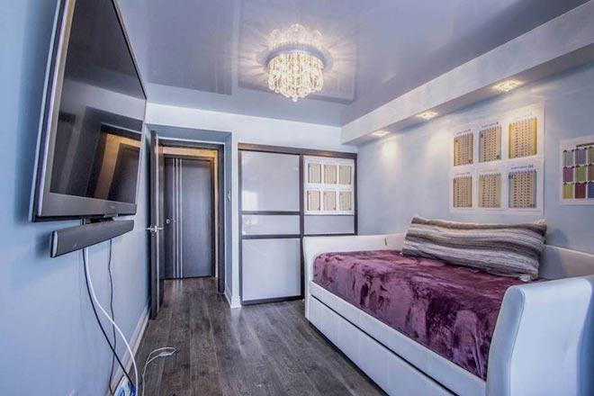 одноуровневый простой натяжной потолок в гостиной с люстрой