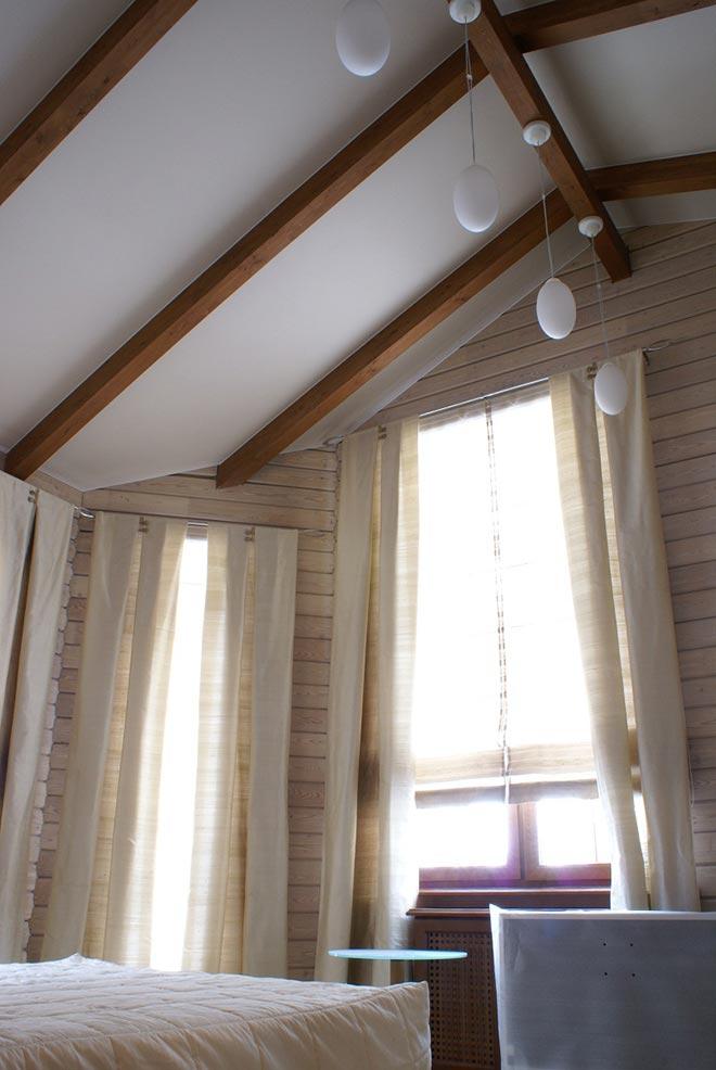 Натяжной потолок в деревянном доме со скатной крышей и балками